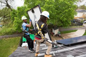 Antwain Nelson (left) and Andre Hinton (right), both workers with Grid Alternatives, install solar panels at a home in Washington DC in May 2016. Photograph by Eric Kruzewski for the Guardian